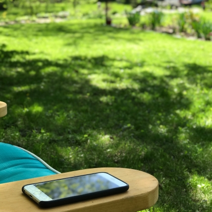 An iPhone sitting on the arm of a lawn chair.